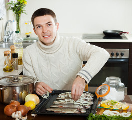 Happy guy cooking trout fish with onion