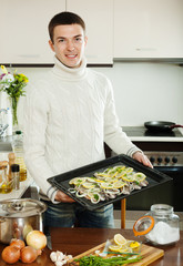 man with raw fish on roasting pan