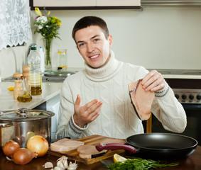 Handsome man holding raw steak of fish