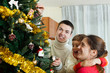 Happy parents and baby girl decorating Christmas tree