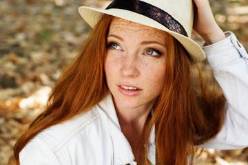 Nice redhead girl in autumn park