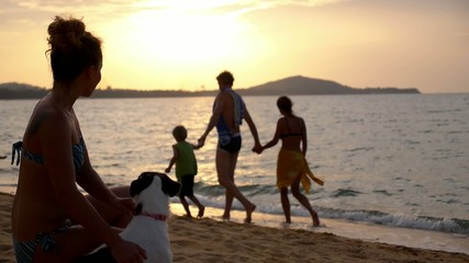 Woman with Dog at Beach and Happy Family in the Background.