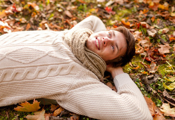 close up of smiling young man lying in autumn park