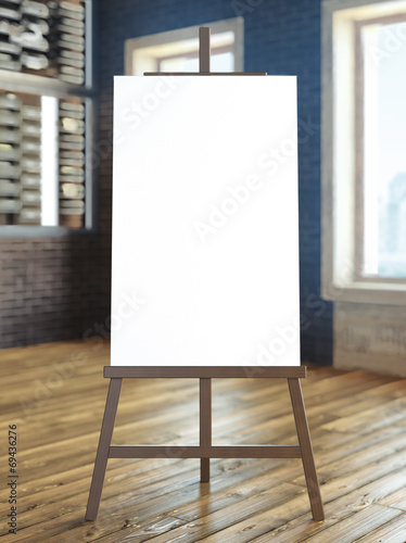 easel with blank canvas in interior - 69436276