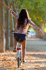 Pretty young girl riding bike in a forest.