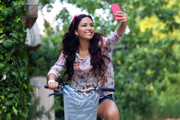 Pretty young girl riding bike and taking a selfie.