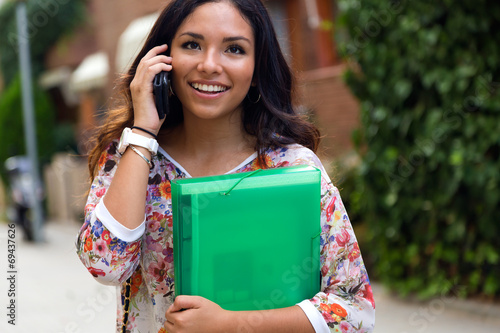 Pretty student girl talking on the phone.