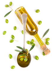 View from above of a olive oil in bottle, in a spoon and raw oli