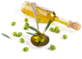 Olive oil in a glass bottle and green olives
