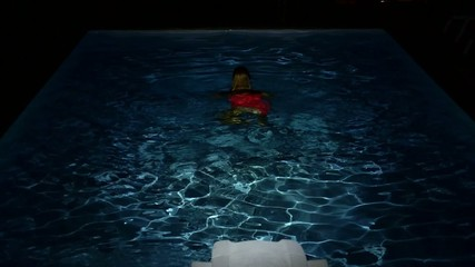 Young Female Swimming in the Pool at Night. Slow Motion.