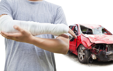 closeup of bandaged arm with blue wrecked car