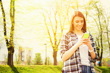 Young woman with smartphone in park in summer