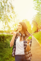 Happy teenage girl with smartphone in park. Candid shot.