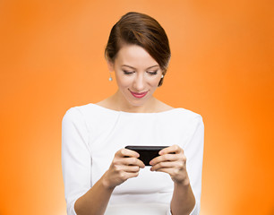 Woman texting on smart phone on orange background