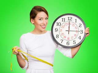 Happy Female holding clock, measuring her waist with tape