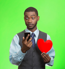 Surprised young man with smart phone and red heart
