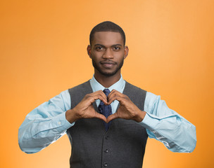 man makes hand shape heart, orange background