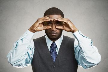 Curious man looking future through binoculars grey background