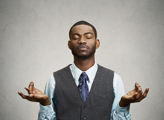 Businessman meditating isolated on grey wall background