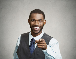 Man laughing pointing finger at someone on grey background