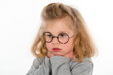 little girl with round glasses looking sad