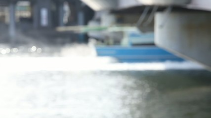 川を通り過ぎる日傘の女性