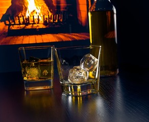 glasses of whiskey with ice near bottle near fireplace