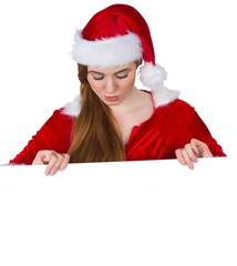 Pretty girl in santa costume showing card