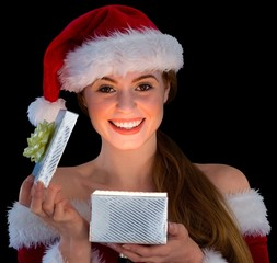 Pretty redhead in santa outfit opening a gift smiling at camera