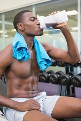 Sporty man drinking protein in gym
