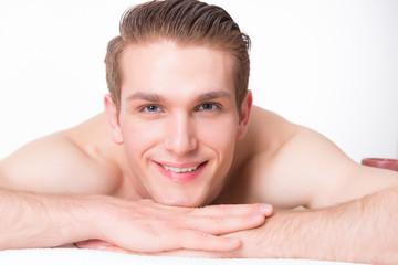 Handsome man lying on the massage desks.