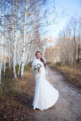 Young beautiful happy bride on autumn winter forest background
