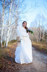 Young beautiful happy slim smiling bride girl woman on autumn wi