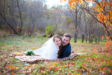 Happy wedding couple in autumn winter forest, lying on plaid