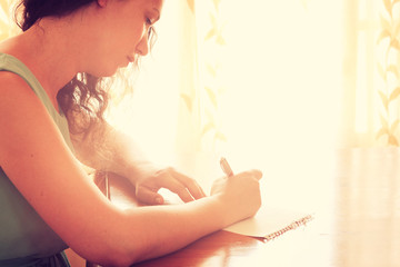 young woman sitting and writing letter near bright window light.