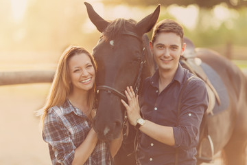 Happy young couple spending time together with their horse