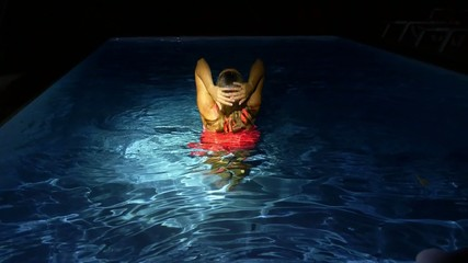 Young Sexy Woman in the Swimming Pool at Night. Slow Motion.