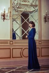 Woman in blue evening dress in luxury interior