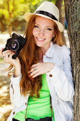 Nice red-haired girl photographer at work