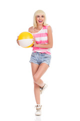 Blonde girl posing with a beach ball