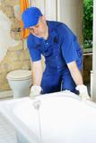 Handwerker montiert Badewanne in Bad
