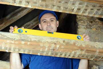 Bauarbeiter mit Wasserwaage im Dachstuhl