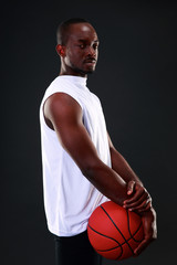 Young african american basketball player over black background