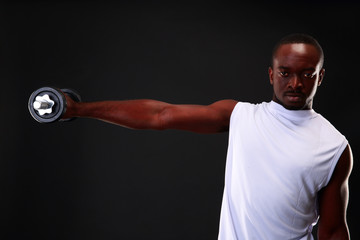 Portrait of african man with dumbbell over black background