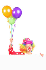 Female clown holding balloons behind a panel