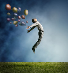 Man jumping up to Sky wit color bright balloon