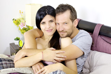 Beautiful happy couple in love smiling hugged in bed