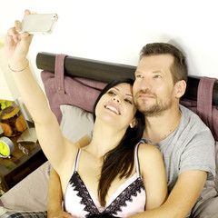 Happy couple taking selfie in vacation in hotel bedroom