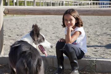 Niña sentada junto a perro