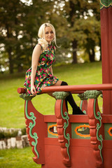 cute woman sitting on handrail at pagoda